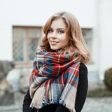 Portrait of an attractive woman with blond hair with a wonderful smile in a black stylish coat with a woolen checkered warm scarf stock images