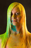 Portrait of attractive woman with green and yellow colors Holi Royalty Free Stock Photography