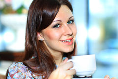 Portrait of attractive woman holding cup at cafe Royalty Free Stock Images
