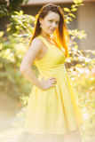 Portrait of attractive woman with long hair holding hand on waist and posing and smiling at camera. Side view of woman in yellow d Royalty Free Stock Photos