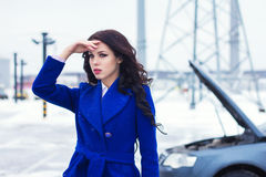 Portrait of attractive woman looking into the distance and waiting for help on the road Royalty Free Stock Photography