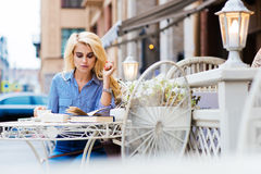 Portrait of an attractive woman with luxury blonde hair reading book while sitting alone in beautiful sidewalk cafe Royalty Free Stock Image