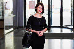 Portrait of attractive woman in a mall. Office worker, beautiful young businesswoman in black dress walking with briefcase in contemporary building. looking and stock photos