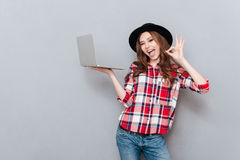 Portrait of an attractive woman in plaid shirt holding pc Royalty Free Stock Image