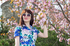 Portrait of attractive woman posing with sakura flowers in park Royalty Free Stock Image