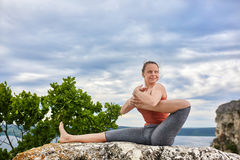 Portrait of the attractive woman is practicing yoga on the rock above river. Stock Photos