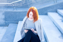 Portrait of attractive woman reading a tablet and sitting outdoors Royalty Free Stock Photos