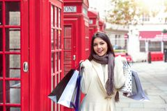 Portrait of a woman with shopping bags in her hand in front of red telephone booths in London, UK royalty free stock images