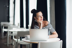 Portrait of an attractive woman sitting in some coffee shop with her laptop and thinking over a subject while looking. Through the window Stock Image