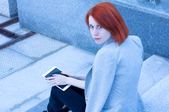 Portrait of attractive woman sitting on the street on the stairs with tablet Royalty Free Stock Images