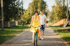 Portrait of attractive woman with stylish haircut and retro look riding on old bicycle and smiling at camera. Man is behind the wo Royalty Free Stock Photo