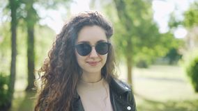 Portrait of attractive woman in sunglasses and trendy leather jacket looking at camera and smiling standing in city park. Portrait of attractive young woman in stock footage