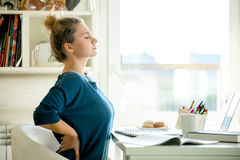 Portrait of an attractive woman at the table backache pose Royalty Free Stock Photo