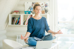 Portrait of an attractive woman at table , lotus pose Stock Images