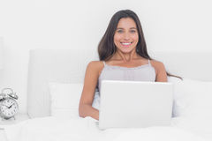Portrait of an attractive woman using her laptop in bed Royalty Free Stock Image