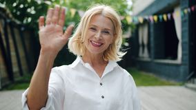Portrait of attractive woman waving hand and smiling standing outdoors stock video