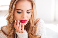 Portrait of an attractive woman wearing red lipstick and sweater. Close up portrait of an attractive young woman wearing red lipstick and sweater indoors Stock Image