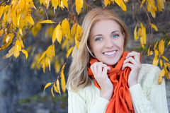Portrait of attractive woman in white sweater smiling against st royalty free stock photo