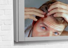 Portrait of attractive worried and concerned Caucasian man looking at bathroom mirror finding himself with gray hair in head feeli royalty free stock photo