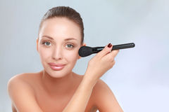 Portrait of attractive young adult woman with make-up brush Royalty Free Stock Images