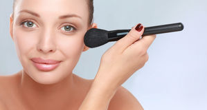 Portrait of attractive young adult woman with make-up brush Royalty Free Stock Photo