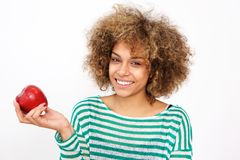 Attractive young african american woman holding an apple stock photo