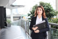 Portrait of attractive young Asian business woman holding document folder and walking in office. royalty free stock images