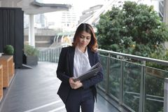 Portrait of attractive young Asian business woman holding document folder and walking in office. Stock Photos
