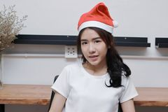 Portrait of attractive young Asian business woman with santa hat smiling in office. Stock Photos