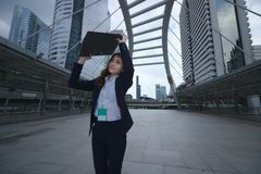 Portrait of attractive young Asian business woman walking and raising document folder at sidewalk of urban city background royalty free stock image