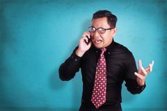 Attractive young businessman talking on his phone, shocked cryin. Portrait of attractive young Asian businessman talking on his phone, getting bad news, shocked Stock Images