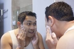 Man Wash his Face in Bathroom stock photography