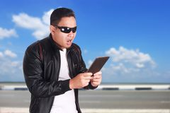 Asian Man Having Surprising News on Tablet. Portrait of attractive young Asian man wearing black leather jacket and sunglasses looking surprising online news on Royalty Free Stock Photography
