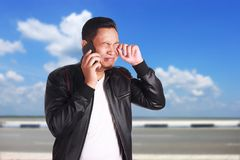 Asian Man Talking on Phone, Sad Crying Expression. Portrait of attractive young Asian man wearing black leather jacket talking on his phone, sad crying Stock Image