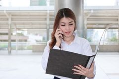 Portrait of attractive young Asian secretary woman talking on phone and looking paperwork in document folder at sidewalk of office.  Stock Image