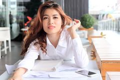 Portrait of attractive young Asian woman with paperwork or charts on the desk in office. Portrait of attractive young Asian woman with paperwork or charts on Stock Photos