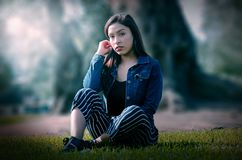 Portrait of an attractive, young and attractive brunette woman sitting on the lawn. royalty free stock photo