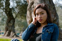 Portrait of an attractive, young and attractive brunette woman sitting on the lawn. royalty free stock photography