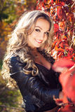 Portrait of an attractive young blond woman biker posing on her Royalty Free Stock Images