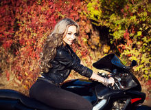 Portrait of an attractive young blond woman biker posing on her Stock Photos