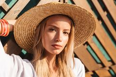 Portrait of attractive young blond woman 20s in straw hat and sw. Imwear posing against wooden beams on sunny summer day stock photo