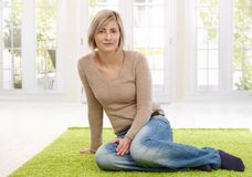 Young woman sitting on floor at home Stock Image