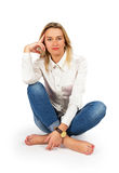 Portrait of attractive young blond woman sitting on floor and lo Royalty Free Stock Image