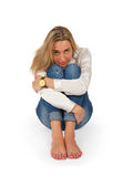 Portrait of attractive young blond woman sitting on floor and lo Royalty Free Stock Photo