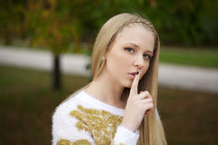 Portrait of attractive young blonde woman with finger on lips. Portrait of attractive girl with finger on lips, concept of student show quiet, silence, secret Stock Photo