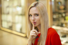 Portrait of attractive young blonde woman with finger on lips. Portrait of attractive girl with finger on lips, concept of student show quiet, silence, secret Royalty Free Stock Photo