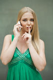 Portrait of attractive young blonde woman with finger on lips Stock Photo