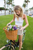 Portrait of a attractive young blonde woman preparing for ride in the park on her classic bicycle Stock Image