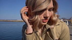 Portrait of attractive young blonde woman in trench with vintage suitcase is sitting on the jacht pier. Portrait of attractive young blonde woman in tranch and stock video footage