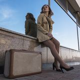 Portrait of Attractive Young Blonde Woman in Trench walking in City with Vintage Suitcase royalty free stock photography